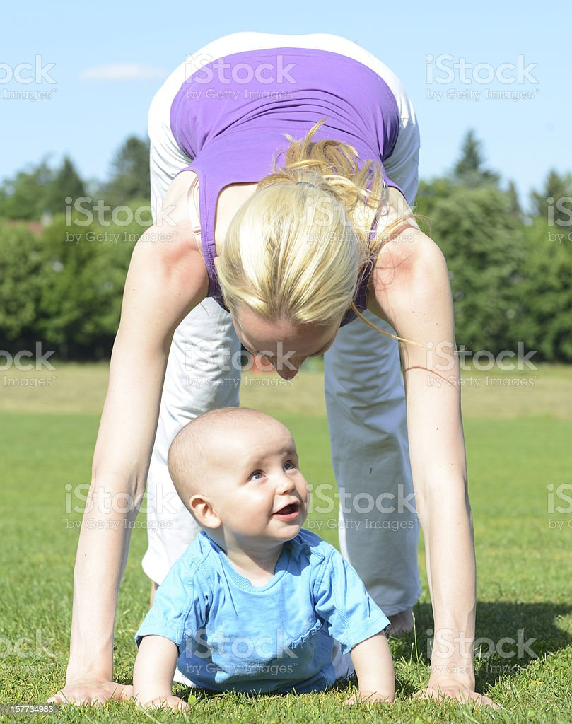 white yoga woman outdoor in nature with baby stock photo