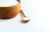White yogurt in wooden bowl with spoon on white background.