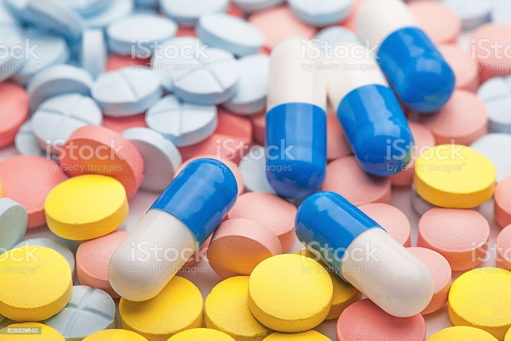 White-blue medical pills on the background of colored medical pi stock photo