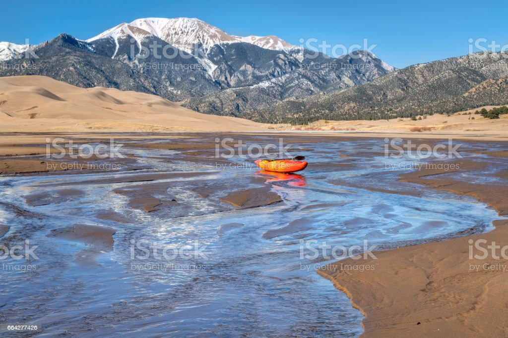 whitewater kayak in shallow water and sand dunes stock photo