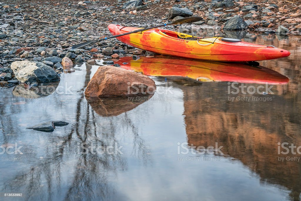 whitewater kayak on rocky shore stock photo