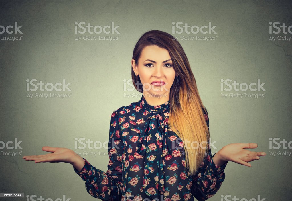 Who cares so what I don't know. Portrait of a pretty young woman shrugging shoulders stock photo