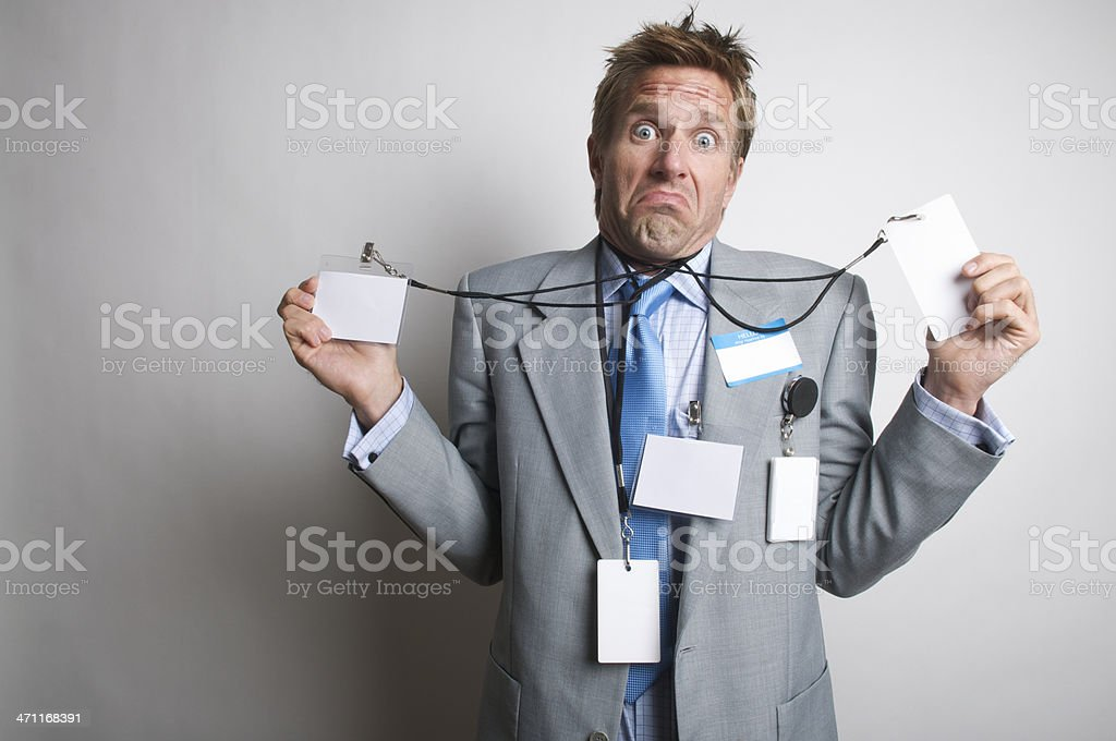 Who The Heck Knows? Confused Businessman Holding Many Name Tags stock photo