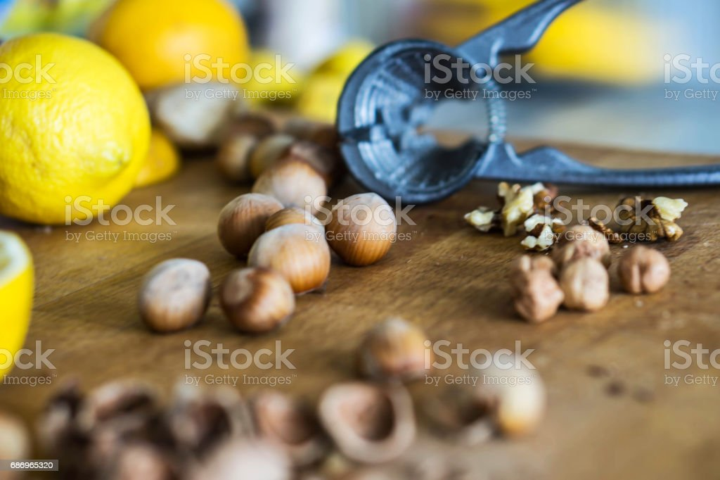 Whole and broken hazelnuts and walnuts on a wooden kitchen board with lemons and oranges on the background stock photo