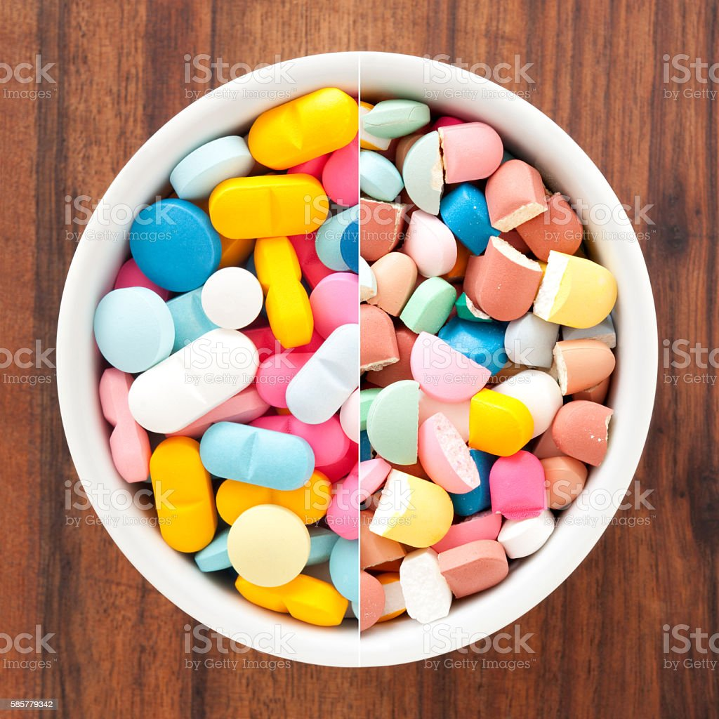 Whole and broken multicolored pills composition stock photo