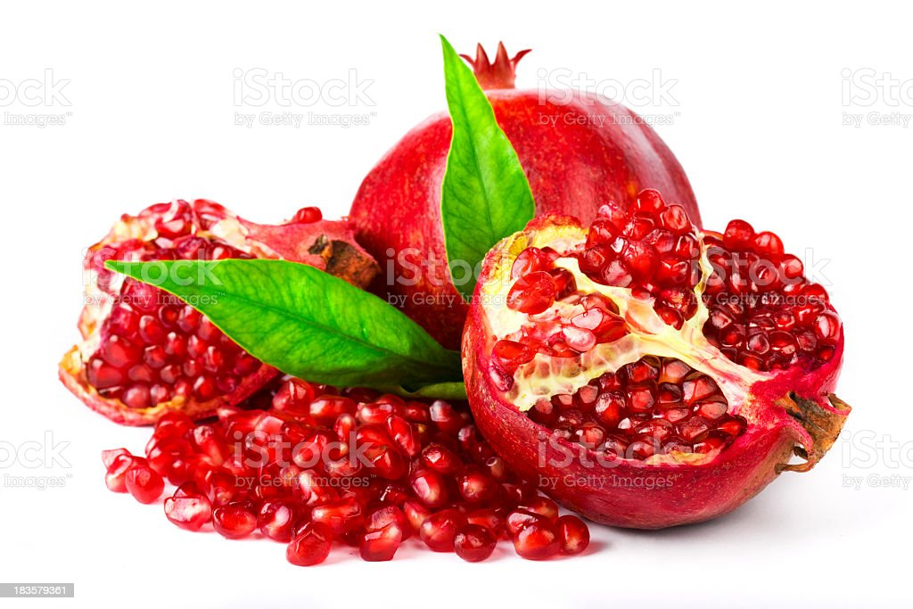 Whole and cracked pomegranate with leaves and seeds royalty-free stock photo