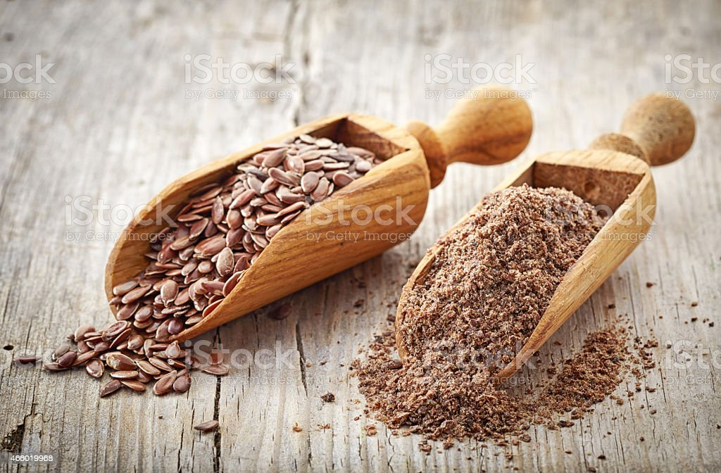 Whole and crushed flax seeds in ladles stock photo