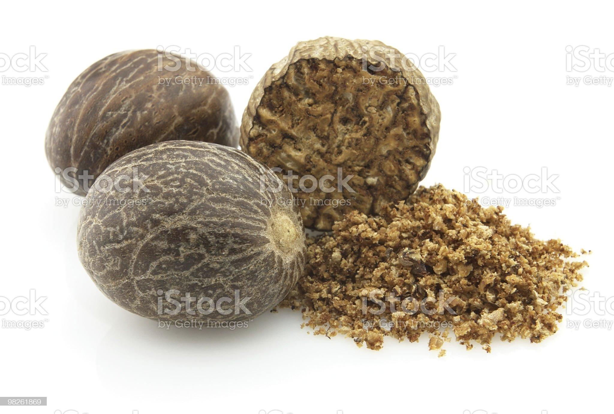 Whole and crushed up nutmeg on a white background royalty-free stock photo