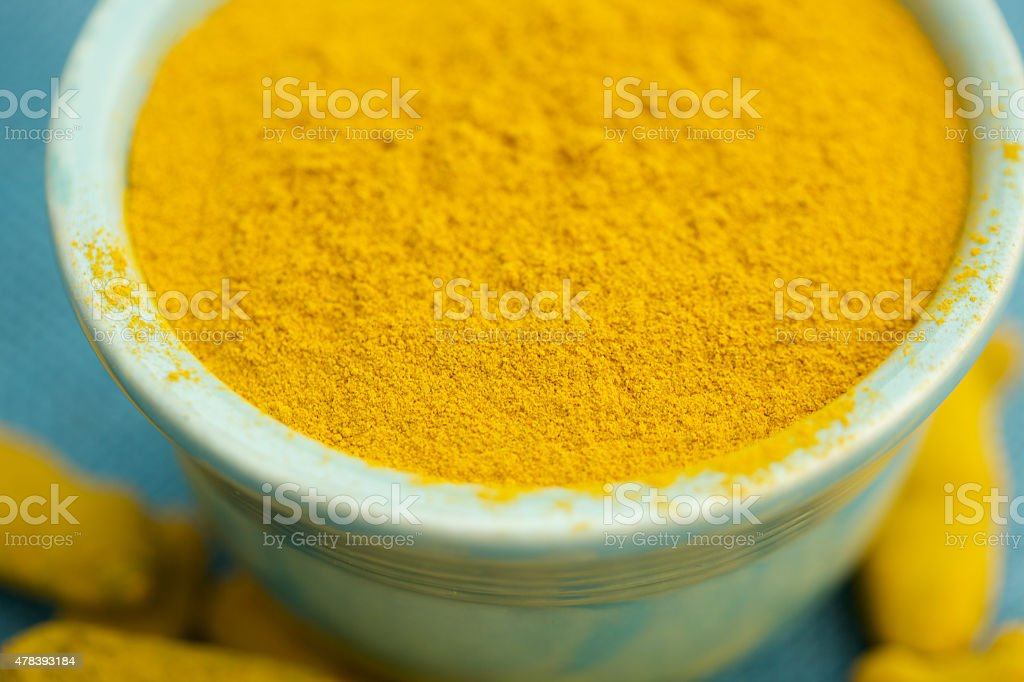 Whole and ground turmeric in bowl stock photo