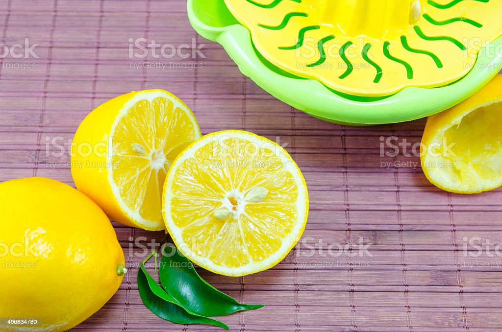 Whole and halved lemons and a squeezer royalty-free stock photo