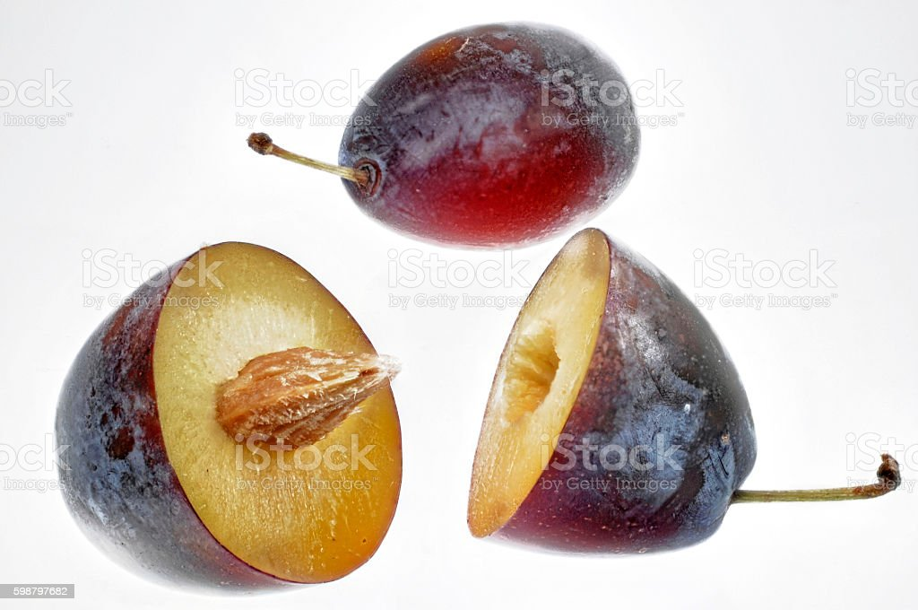 whole and halved plums stock photo