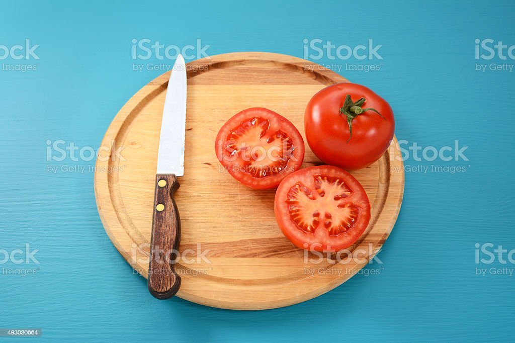 Whole and halved tomato with kitchen knife stock photo