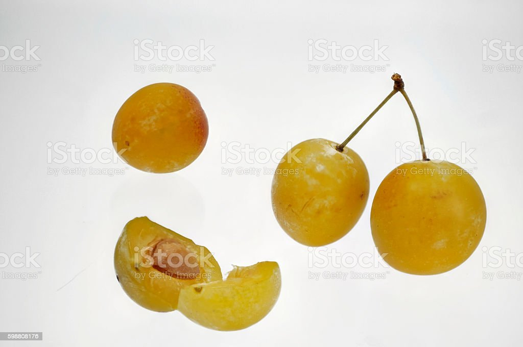whole and halved yellow Mirabelle stock photo