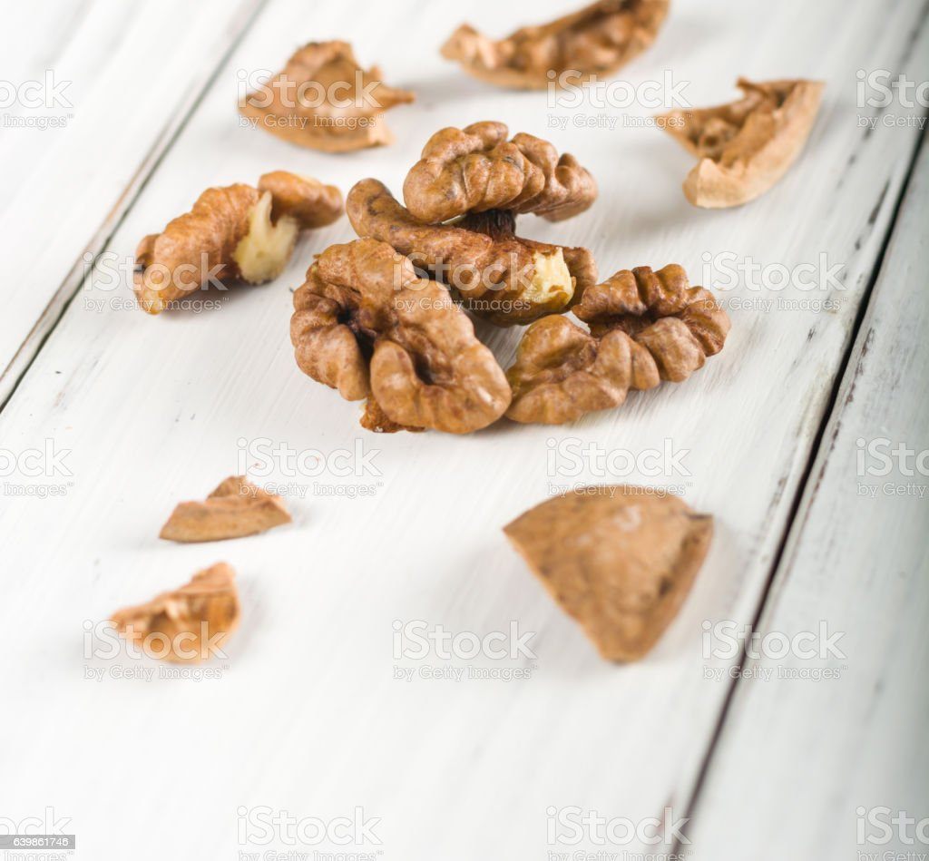 Whole and shelled walnuts on a white wooden background. stock photo