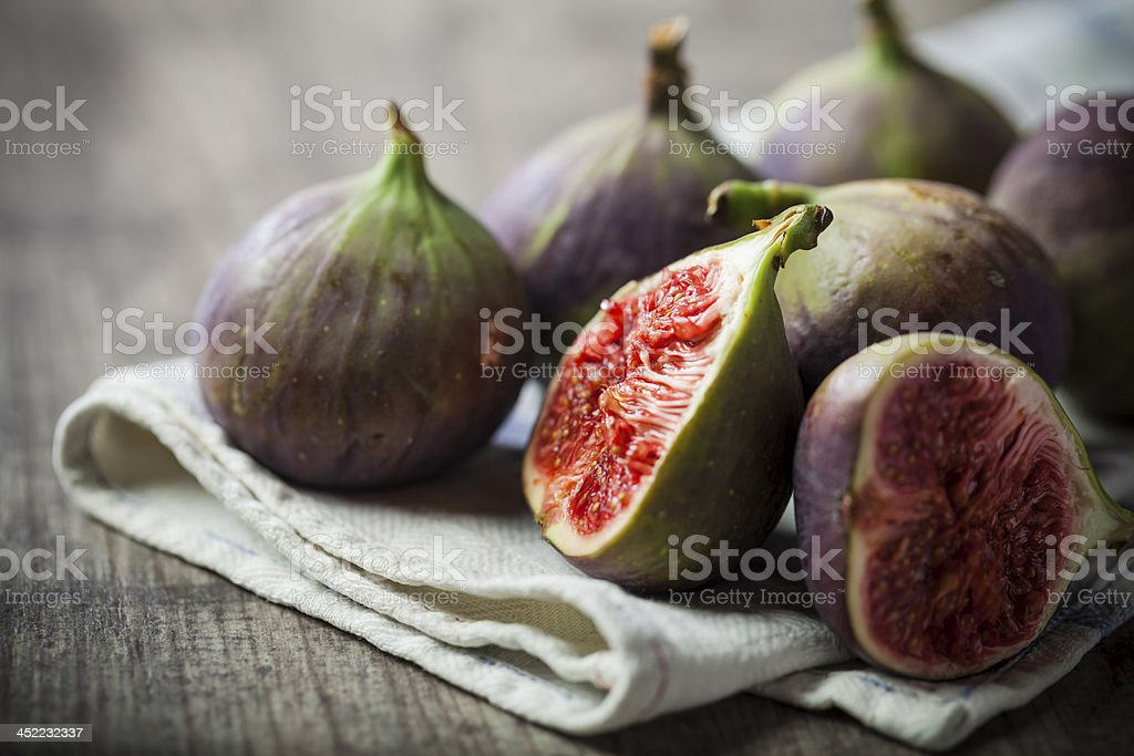 Whole and sliced figs on a folded linen on wood table stock photo