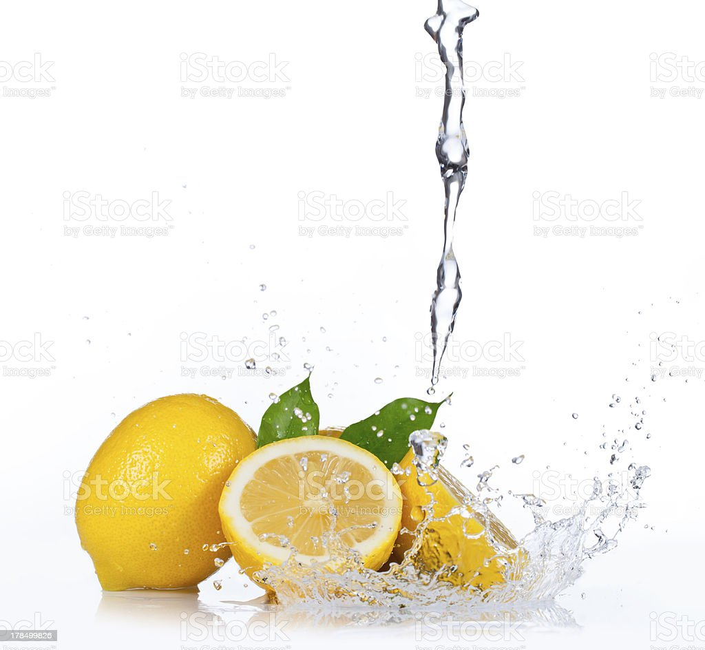Whole and sliced lemons underneath pouring liquid stock photo