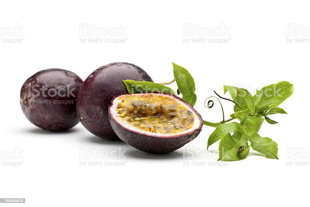Whole and sliced passion fruits with leaves and tendrils stock photo