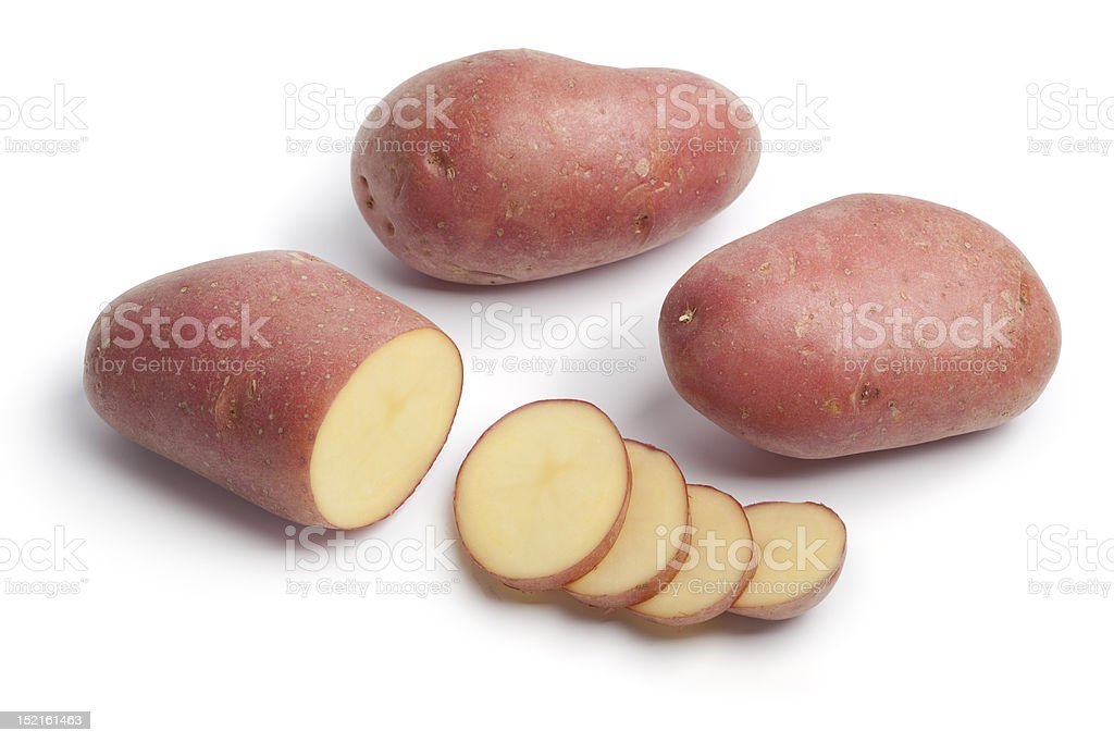 Whole and sliced Roseval potatoes stock photo