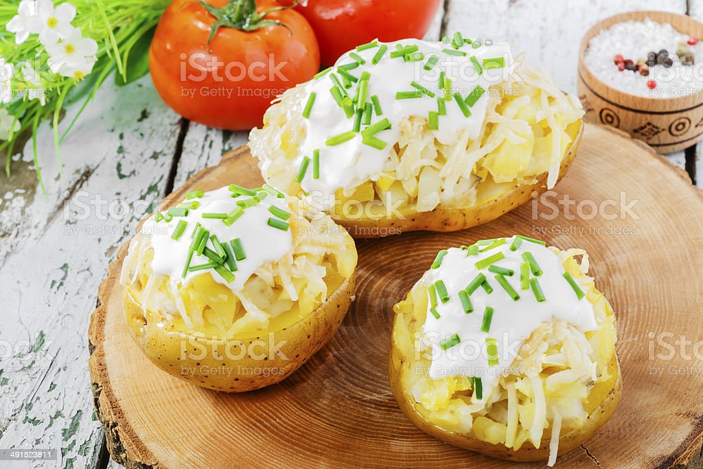 whole baked potato with cheese and sauce royalty-free stock photo
