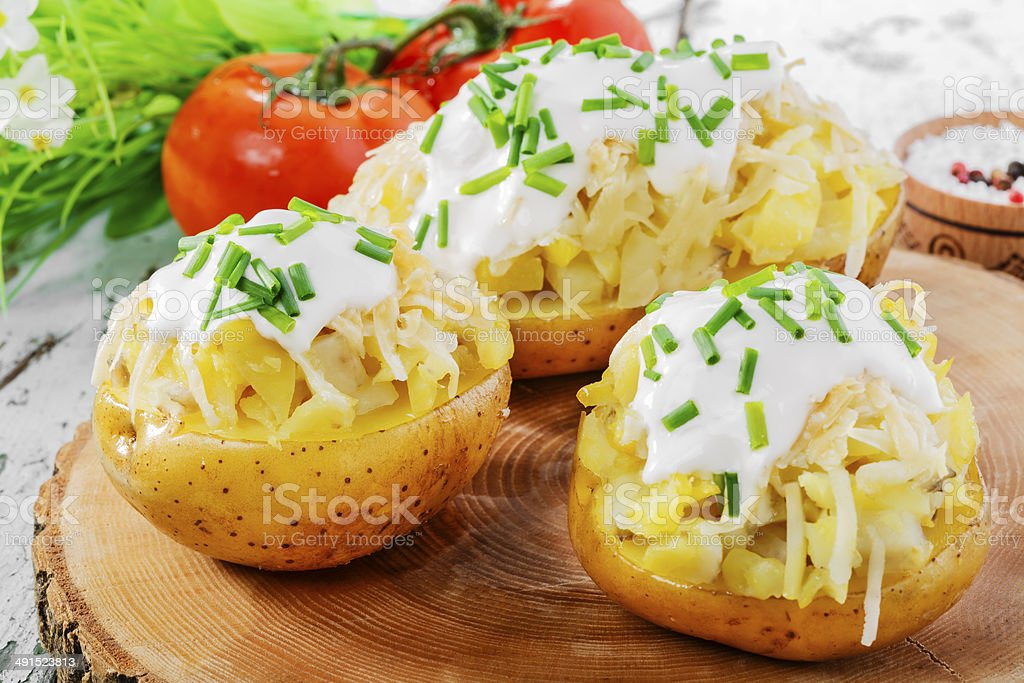 whole baked potato with cheese and sauce stock photo