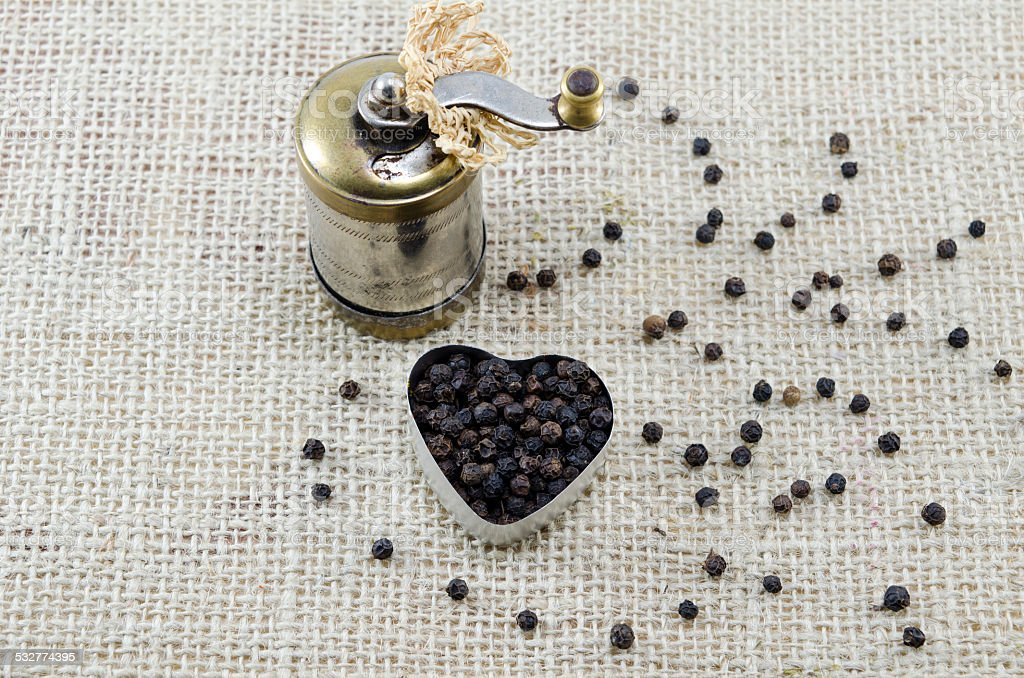 Whole black peppercorns and a pepper grinder royalty-free stock photo