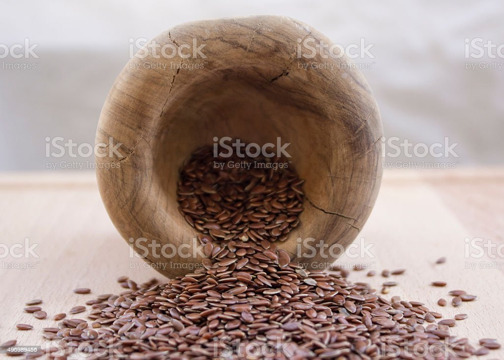 Whole brown flax seeds on wooden olive plate and bowl stock photo