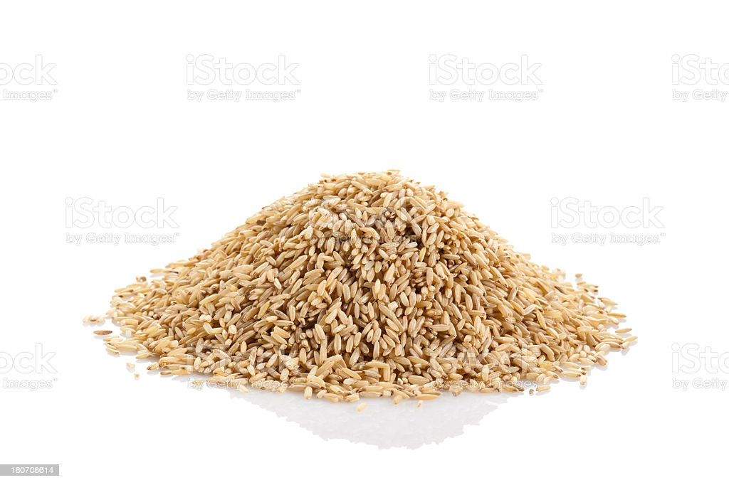 Whole brown rice against white background stock photo