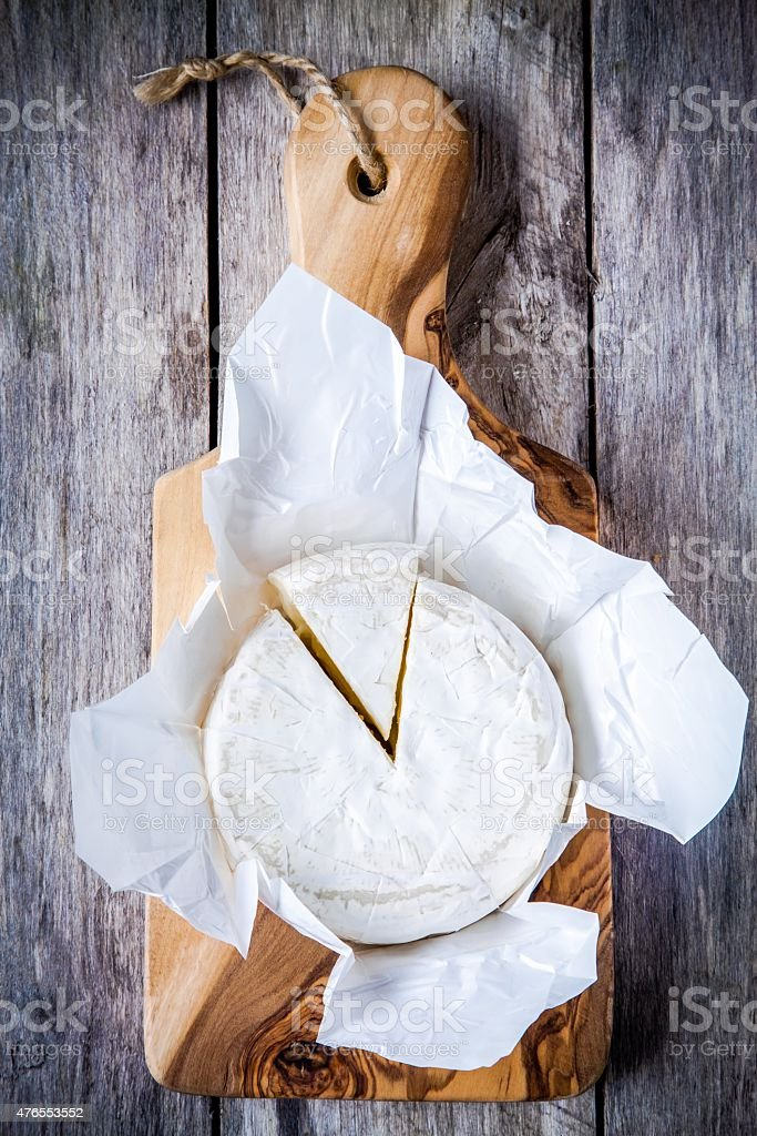 Whole Camembert cheese and portion stock photo