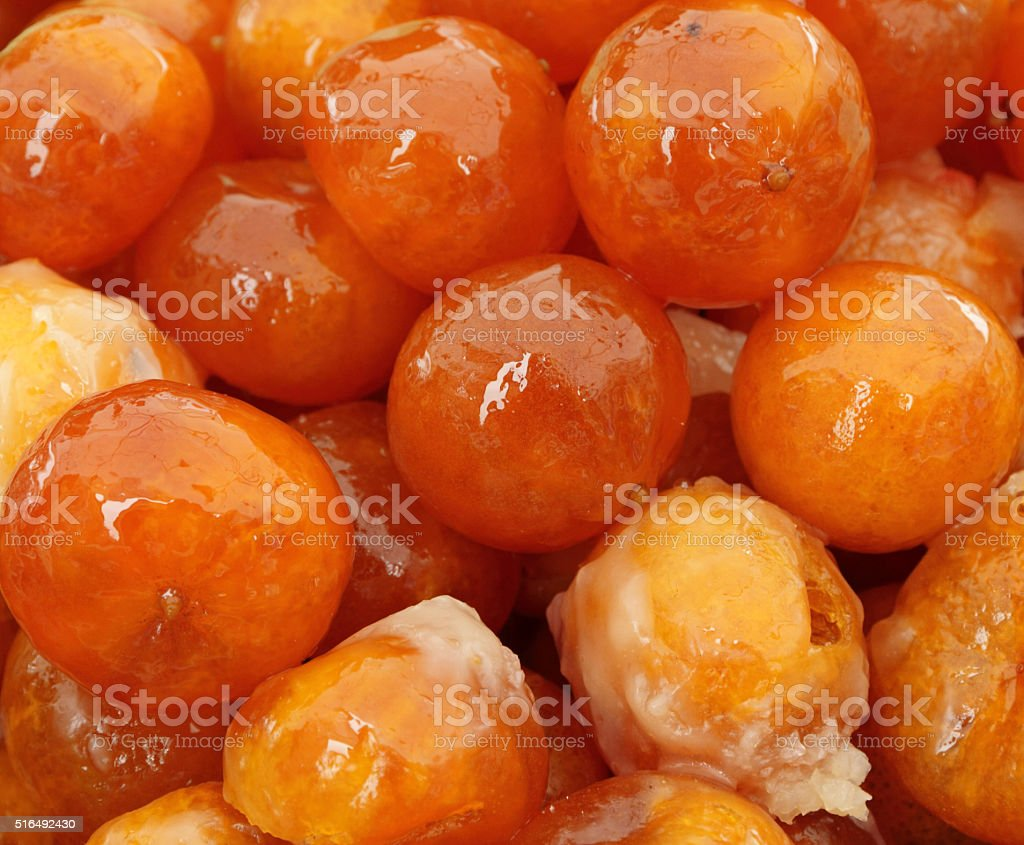 whole candied mandarin fruits as background stock photo