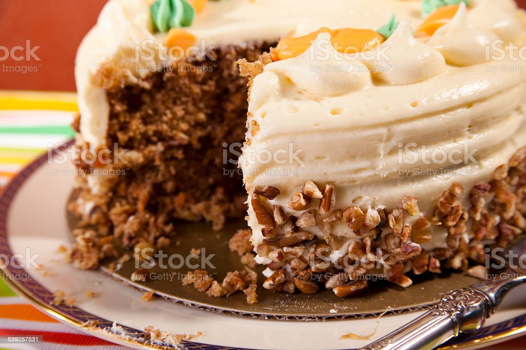 Whole carrot cake, icing and chopped pecans. Piece cut, sliced. stock photo