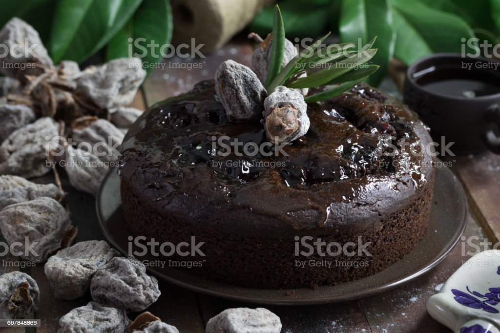 Whole chocolate cake on dark brown  wooden table with coffee stock photo