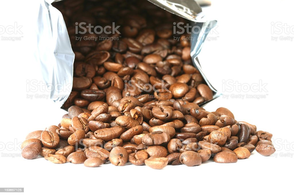 Whole coffee beans scattered and bag on white background royalty-free stock photo