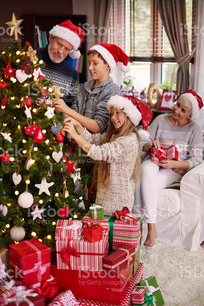 Whole family dressing a christmas tree stock photo