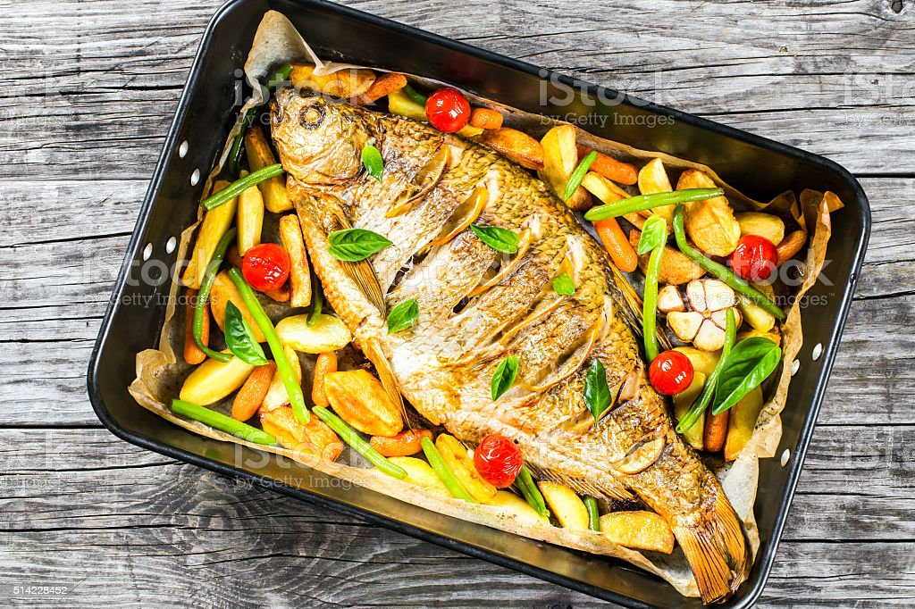 whole fish baked in a baking dish, top view stock photo