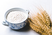 Whole flour in bowl with wheat ears on white background