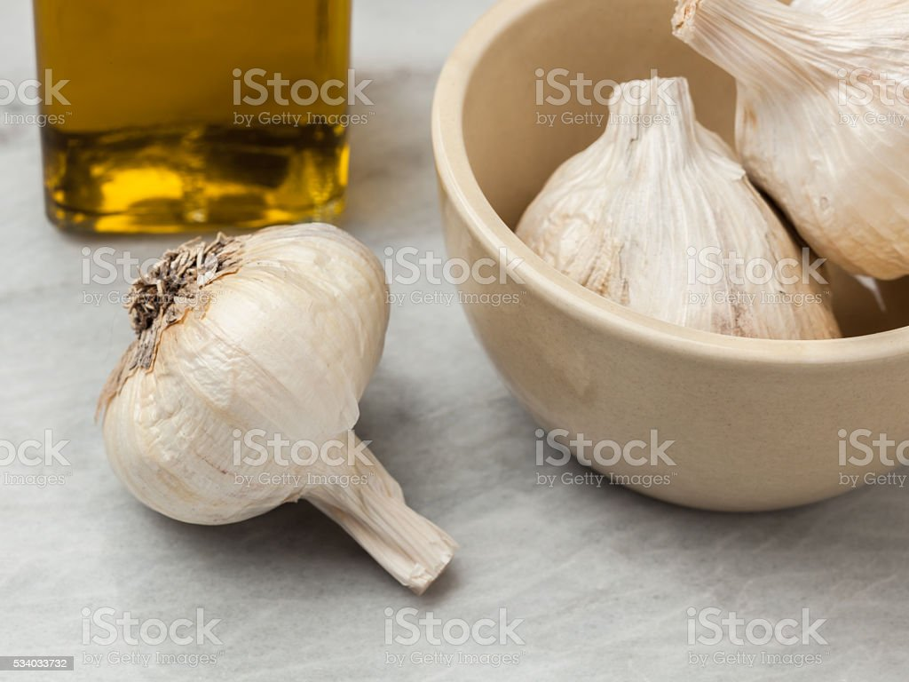 Whole fresh garlic cloves and olive oil stock photo
