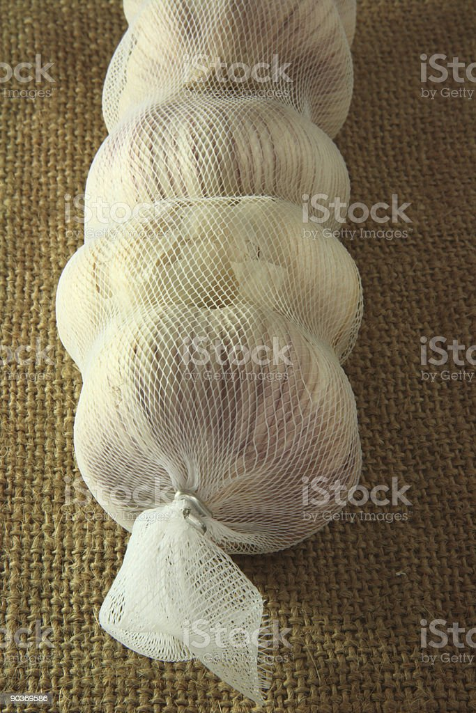 whole garlic bulbs in a net royalty-free stock photo