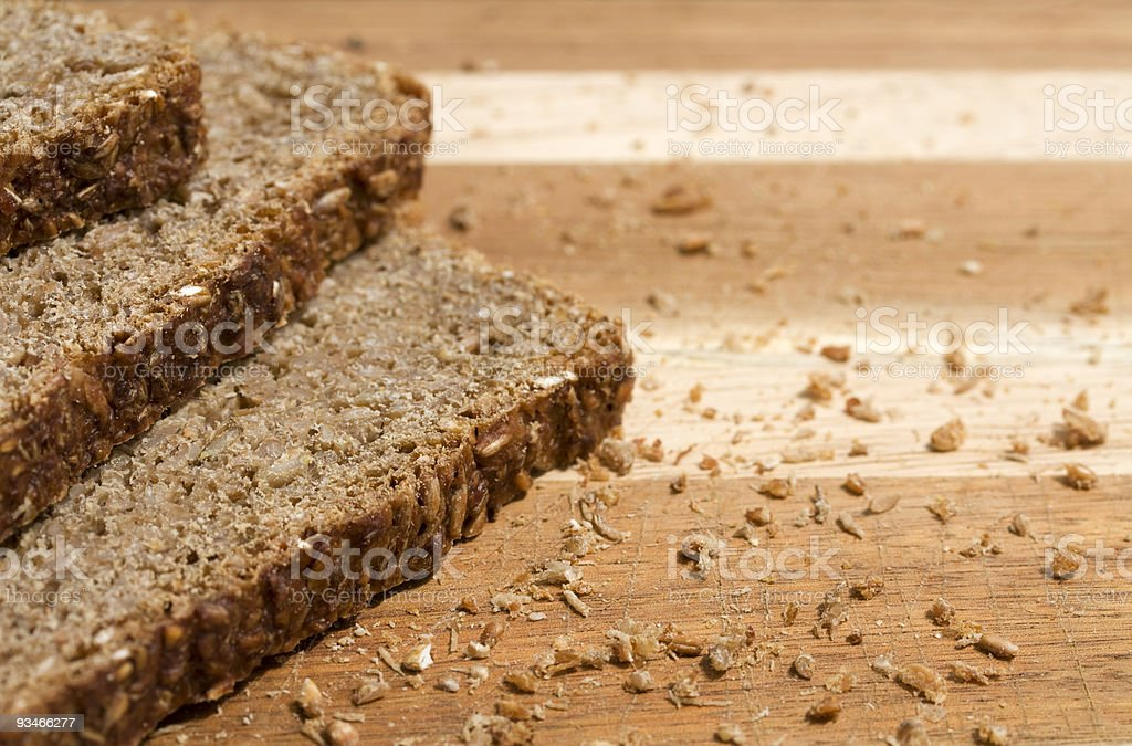 Whole grain bread slices with crumbs on a cutting board. royalty-free stock photo