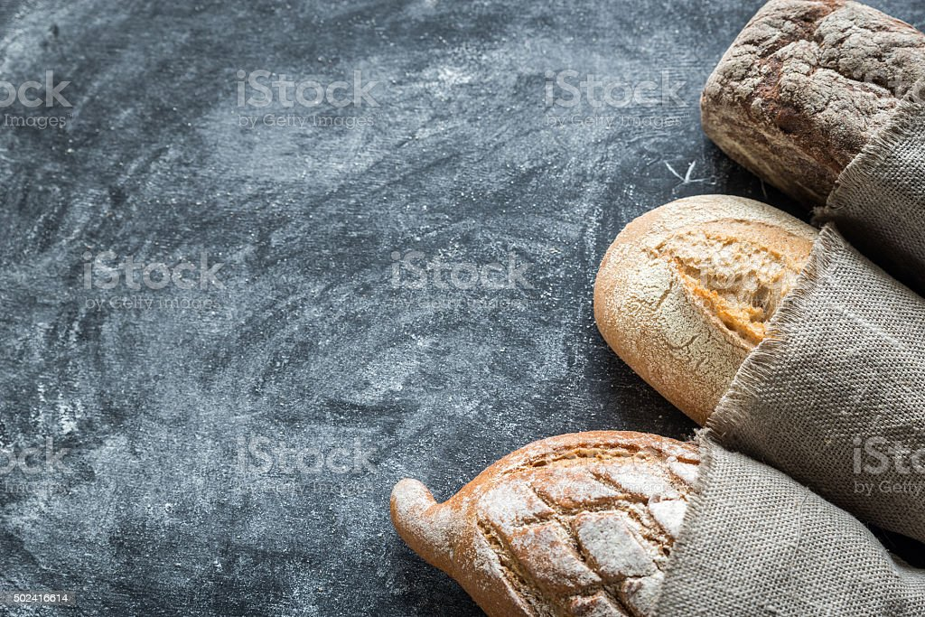 Whole grain breads on the dark wooden background stock photo