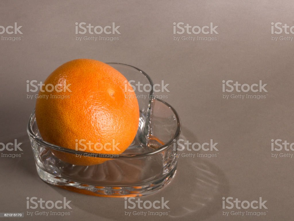 Whole Grapefruit in Heart Shaped Glass Bowl stock photo