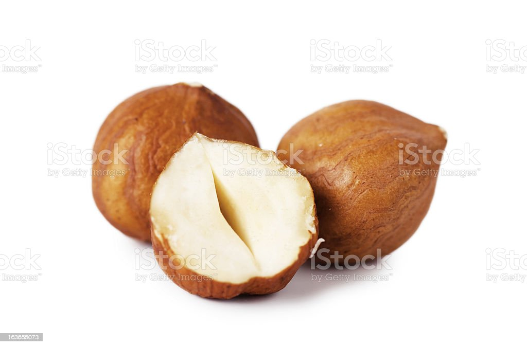 2 whole hazelnuts and 1 half hazelnut on a white background stock photo