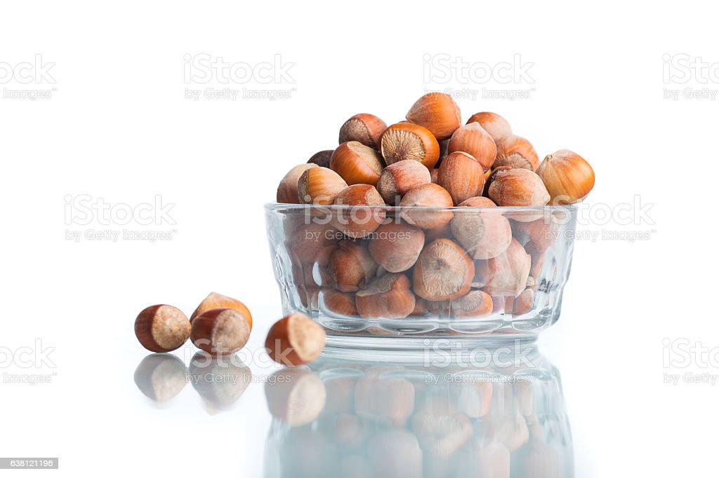 whole hazelnuts in a glass bowl with green leaves stock photo