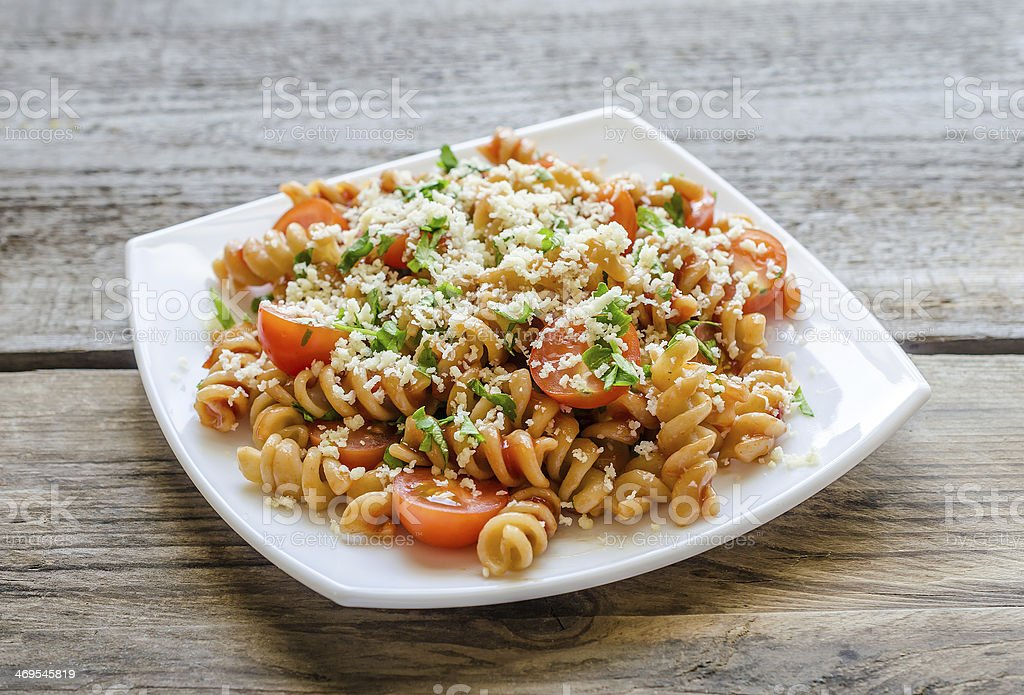 Whole heat fusilli pasta with cheese and cherry tomatoes stock photo