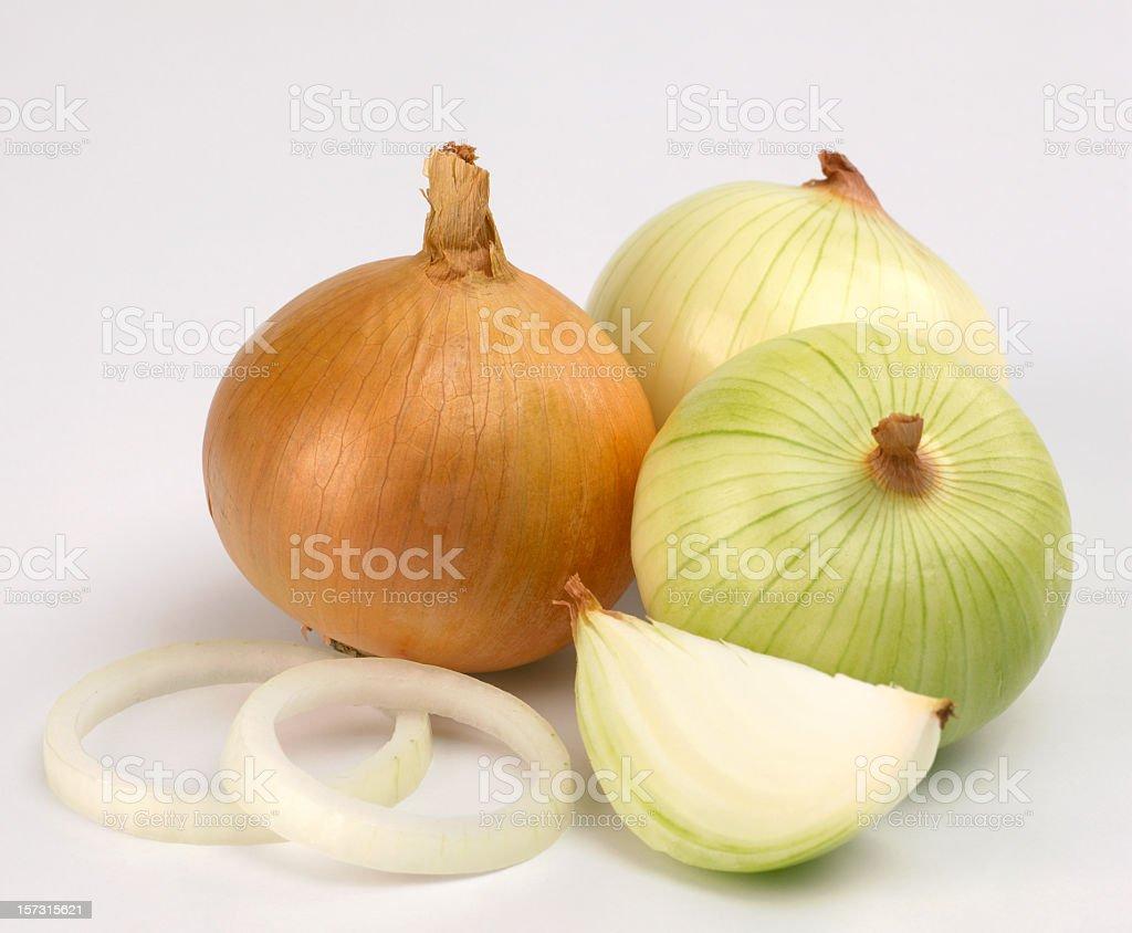 Whole onions unpeeled and a half onion peeled off stock photo