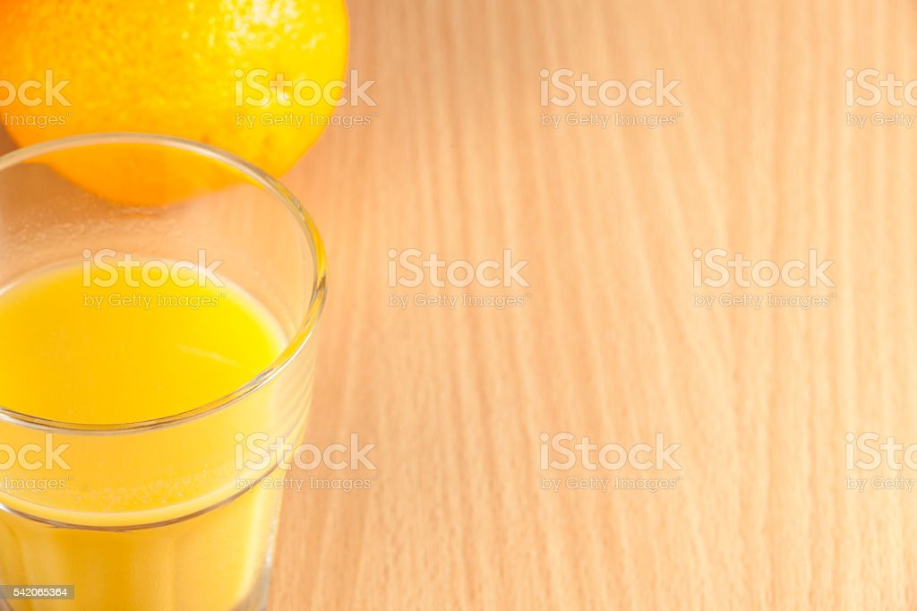 Whole orange and a glass of juice on breakfast table stock photo