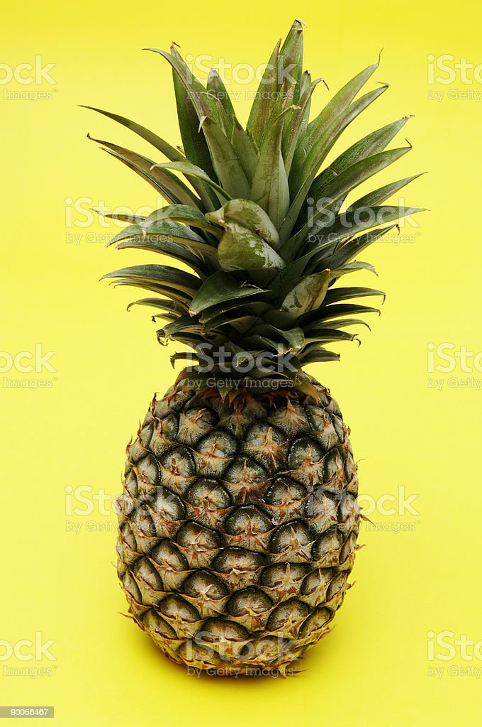 whole pineapple isolated against yellow stock photo