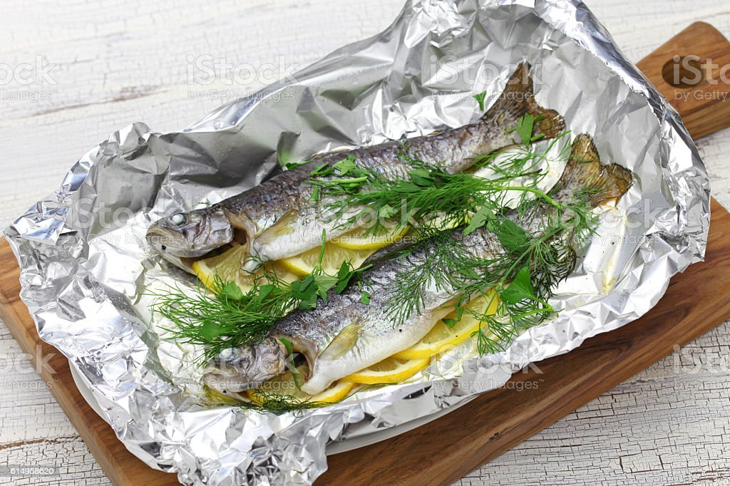 whole rainbow trout baked in foil stock photo
