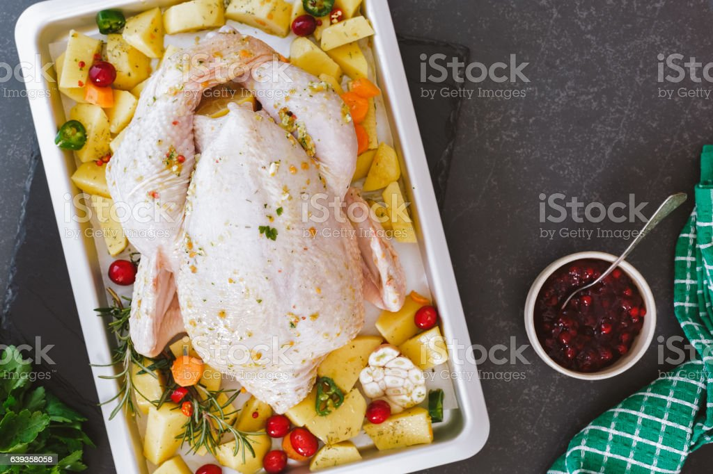 Whole raw chicken with cranberries and vegetables stock photo