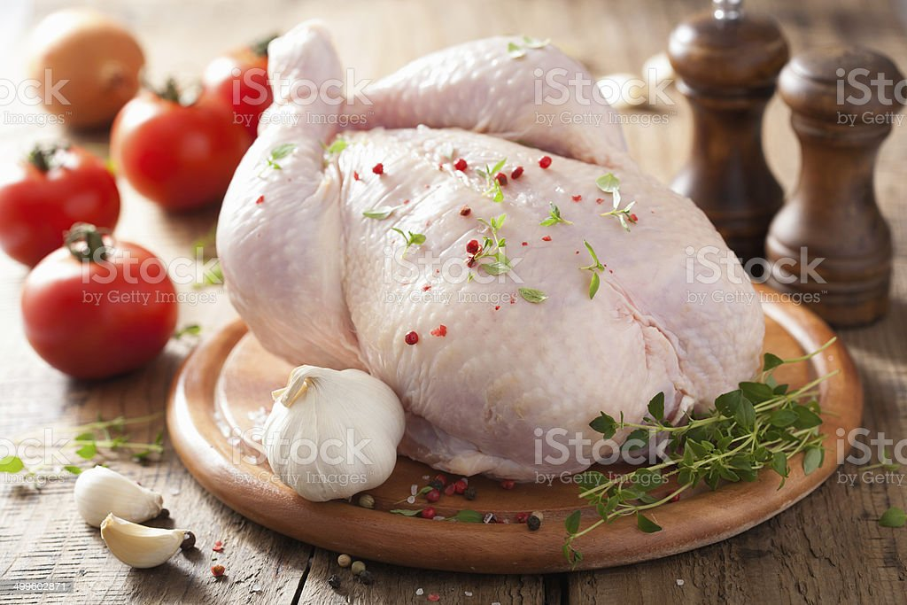 whole raw chicken with rose pepper and thyme stock photo
