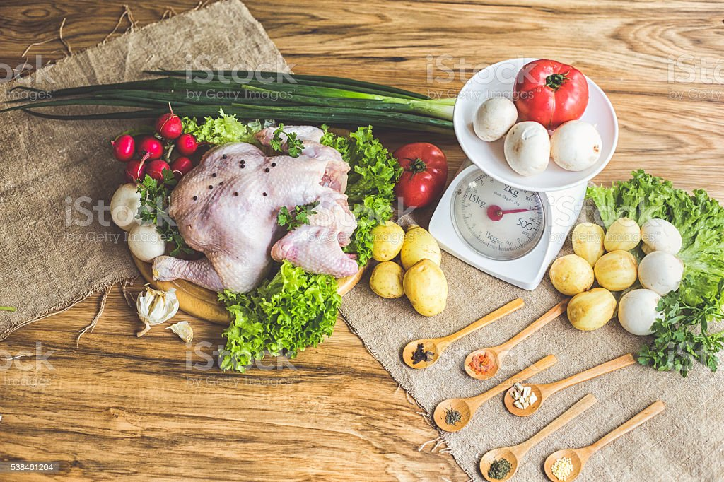 Whole raw chicken with vegetables and kitchen scales stock photo